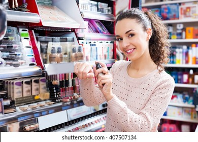Positive female buying CC cream in makeup section