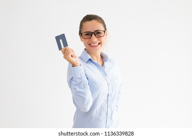 Positive female cardholder happy to receive cash back. Young Caucasian woman in formal shirt raising hand with empty plastic card and posing. Money, benefit concept