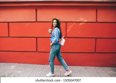 Positive female with coffee to go smiling near urban setting enjoying summer vacations journey for exploring world, happy Caucasian woman with takeaway cup dressed in fashionable apparel rejoicing