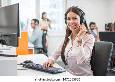 Positiver weiblicher Kundendienstmitarbeiter mit Headset im Call Center