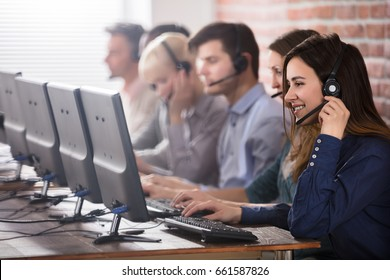 Positive Female Customer Services Agent With Headset Working In A Call Center