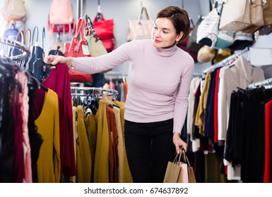 Positive female deciding on pretty blouse in womens cloths shop