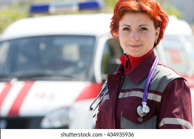 Positive female doctor paramedic on ambulance vehicle background