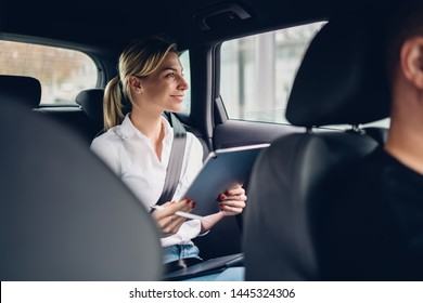 Positive female economist working with accounting via modern portable pc during car trip to business meeting, happy successful woman smiling while looking in automobile window from backseat