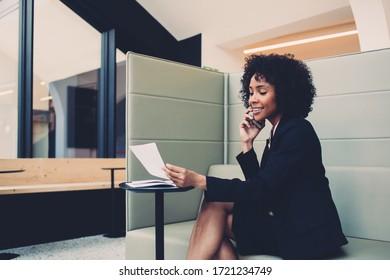 Positive Weibchen in formalem Verschleiß zufrieden mit Finanzbericht-Überprüfung während des Handy-Anrufs, florierende Eigentümer lächeln Lese-Informationen aus leeren Papier während Gespräch mit Partner über Handy