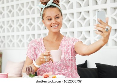 Positive female with freckled skin, holds mug with beverage, eats dessert, poses for making selfie and sending photo for friends or to upload in social networks. People and modern technologies concept