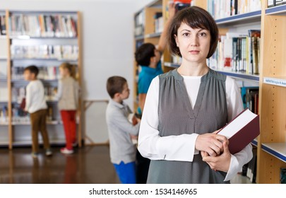 Positive female librarian standing near bookshelves with book in hands