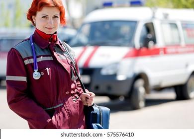 Positive female paramedic with ambulance bag on ambulance car background outdoors