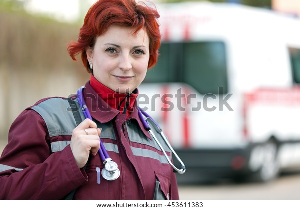 Positive female paramedic with ambulance bag outdoor