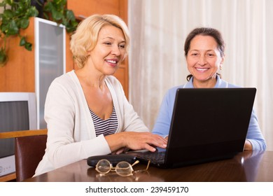 Positive female pensioners sitting with laptop indoor. Focus on blonde