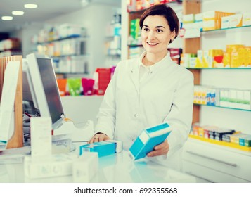 Positive female pharmacist offering help in choosing at counter in pharmacy