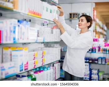 Positive female pharmacist suggesting useful body care products in pharmacy