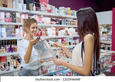 Positive female seller giving purchase to elegant customer in cosmetics store. Young brunette buying present and  paying with credit card in shop. Concept of payment and purchasing.