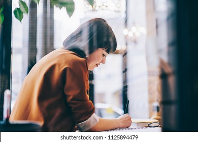 Positive female student sitting at table and enjoying course work and education indoors, successful hipster girl writing essay with excited idea in notebook spending time at university campus