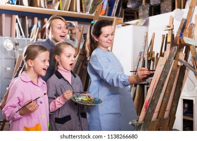 Positive female teacher giving master class during painting class at art studio