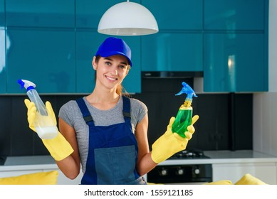 Positive female worker of professional cleaning service makes a choice between different cleaning agents on the background of modern cuisine. House cleaning service concept.