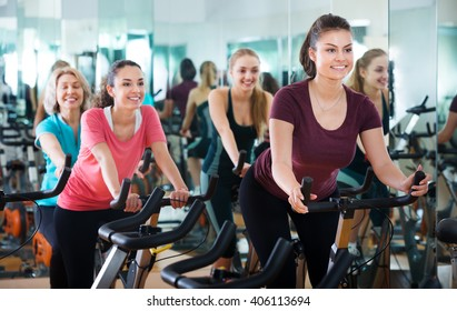 Positive females of different age training on the exercise bikes together in the modern fitness club