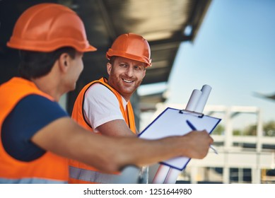Positive friendly builder in orange helmet looking at his coworker and smiling while standing next to him