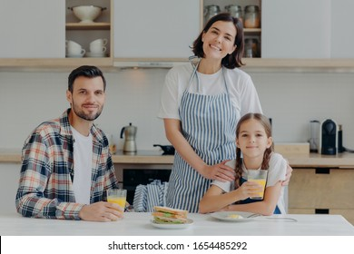 Positive friendly father, mother and their small daughter being in good mood, spend time together, pose at kitchen, gather to have breakfast, enjoy domestic atmosphere and day off. Time to eat
