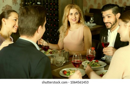 ?heerful positive  friends having dinner and drinking red wine in restaurant