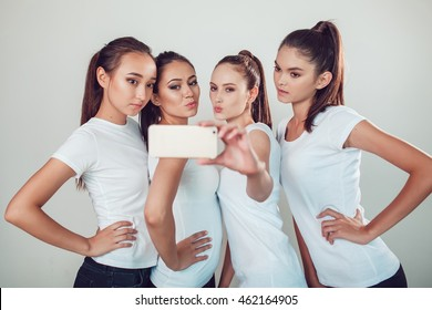 Positive friends portrait of four happy girls making selfie, sure funny faces, grimaces, joy, emotions, casual style, pastel colors, white wall. crazy funny woman. White background.