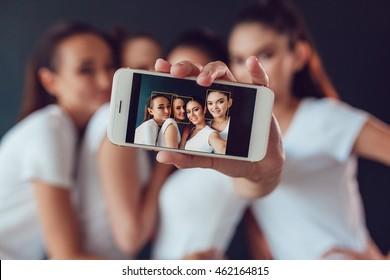 Positive friends portrait of happy girls making selfie, sure funny faces, grimaces, joy, emotions, casual style, pastel colors. Dark background.