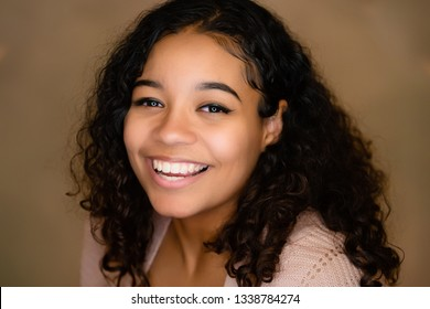 Positive, fun, happy attitude. Extremely happy young lady with curly hair and grinning broadly showing teeth while posing for the camera, fashion ringlight catchlight in eyes