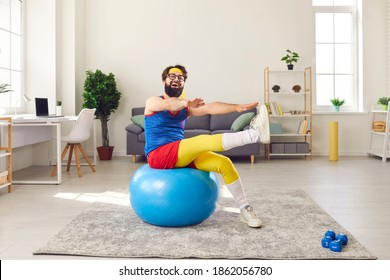 Positive funny bearded young sportsman in blue, red and yellow retro sportswear doing fitness exercise sitting on a fit ball, laughing and having fun during sports workout at home