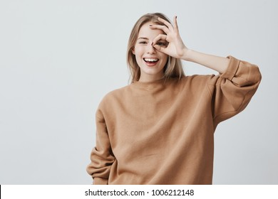 Positive funny blonde girl in casual clothes shows ok sign, laughs at camera, demonstrates that everything is fine, agrees. Cheerful woman gestures indoors. Body language and human emotions