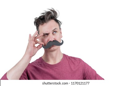 Positive funny man holding his fingers with funny cardboard black mustache, isolated on white background. Look over there!