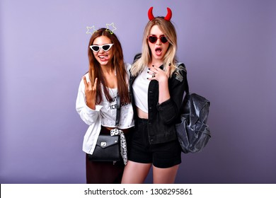 Positive funny portrait of the pretty American students women enjoy their party, youth hipster clothes, crazy carefree easy going mood, two best friends girls.