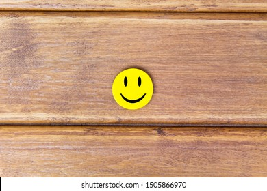 Positive Funny smiley face on a wooden background. Copy space for advertising and texts