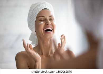 Positive funny young woman laughing while applying facial cream reflecting in mirror, happy attractive lady put moisturizing nourishing creme doing morning routine in bathroom, skin care concept