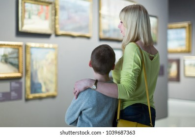 positive germany  mother and son looking at paintings in halls of museum