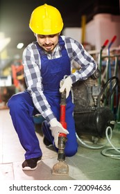 positive germany working man practicing his skills with pneumatic drill at workshop