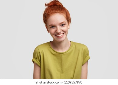 Positive ginger femae with freckled skin, broad smile, dressed in casual green t shirt, isolated over white background, expresses happiness as has date with boyfriend. Red haired teenager has weekend