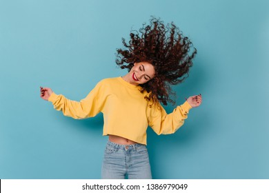 Positive girl in bright sweatshirt plays hair, laughs and dances on blue isolated background