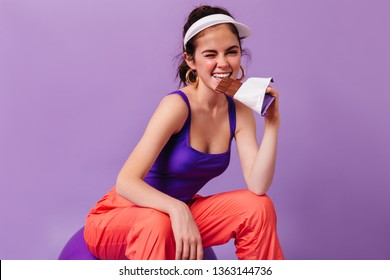 Positive girl in great mood bites chocolate. Woman in white cap and bright sports outfit posing on fitball