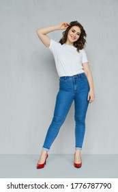 Positive girl in jeans, white t-shirt and red stilettos posing near the wall holding hand near head