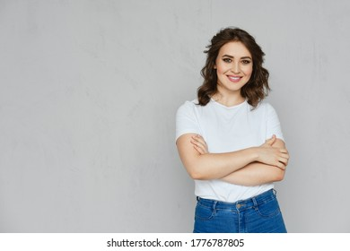 Positive girl in jeans, white t-shirt and red stilettos posing near the wall holding crossed hands on chest
