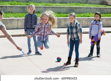 Positive girl jumping while jump rope game with friends outdoor
