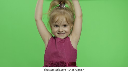 Positive girl looking to a camera in purple dress. Hands up. Happy four years old girl. Pretty little blonde child. Make faces and smile. Place for your logo or text. Green screen. Chroma Key
