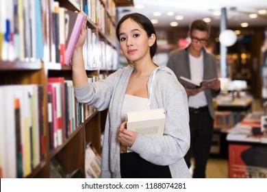 positive girl looking for interesting books on rack in bookshop