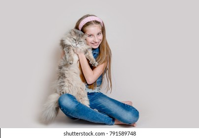 Positive girl playing with cat on grey background