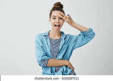Positive girl shows her emotions. Indoor shot of attractive slender caucasian female student sticking out tongue and showing v sign over forehead, being in good mood over gray background