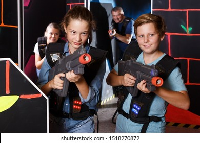 Positive  girls and boys holding laser guns at other players during lasertag game with parents indoors