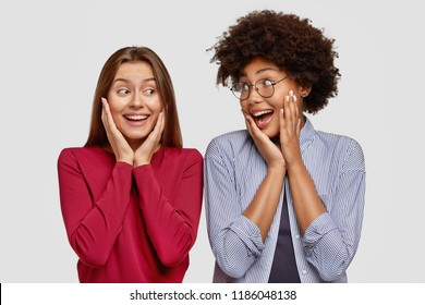 Positive girls of different races, keep hands on cheeks, being in high spirit, rejoice meeting, pose against white background. Happy dark skinned woman looks joyfully at best Caucasian friend
