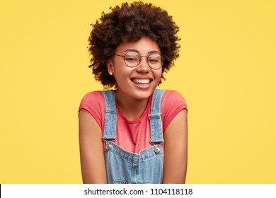 Positive glad African American female has broad smile, wears spectacles, dressed in denim overalls, poses against yellow background. Pretty delighted woman poses in studio alone. Emotions concept