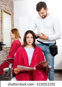 Positive glad cheerful smiling young man hairdresser cuts hair of young woman with magazine at salon
