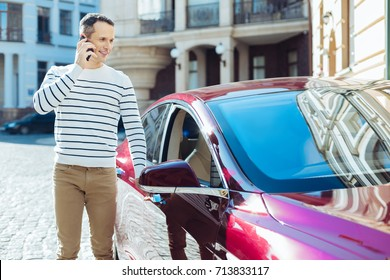 Positive good looking man getting into his car